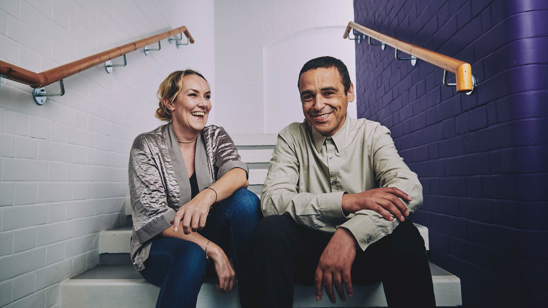 a woman and a man sitting on the stairs laughing
