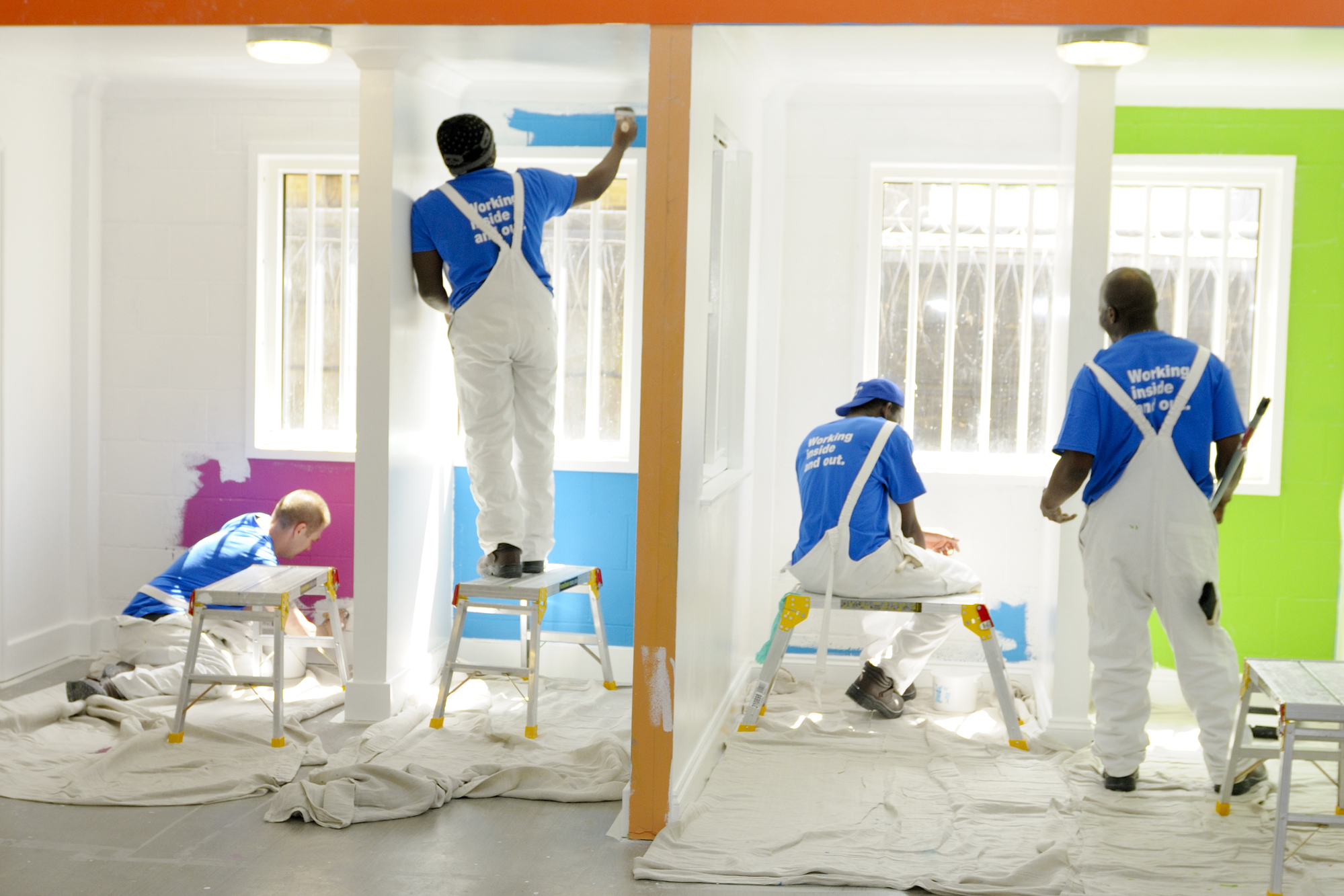 Men painting walls with colourful paint