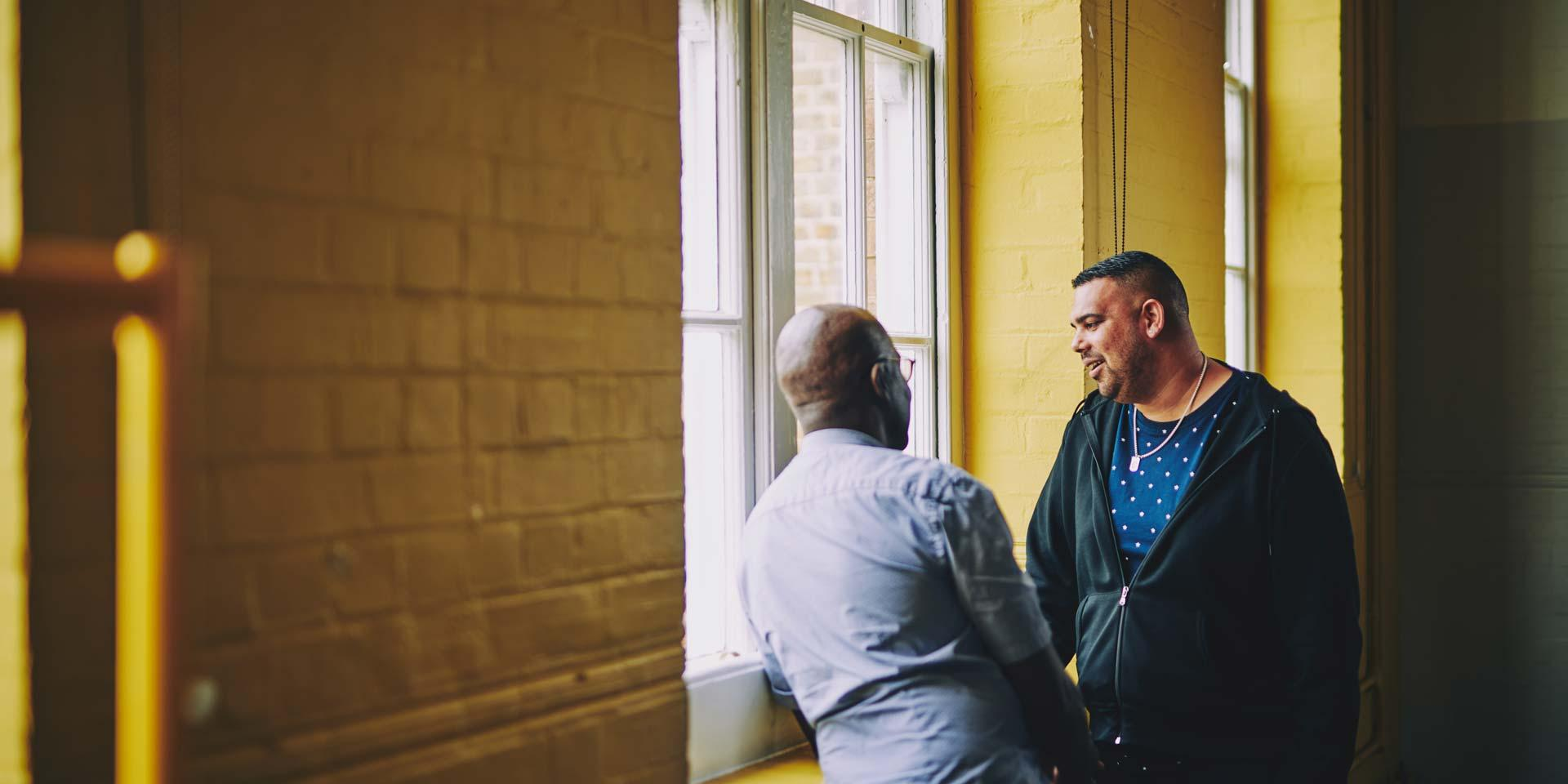 Two men are having a conversation by a window