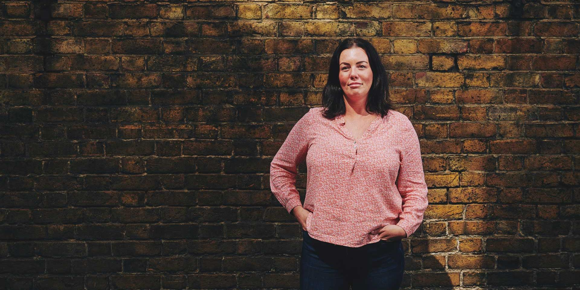 woman standing in front of a wall with her hands in her pockets