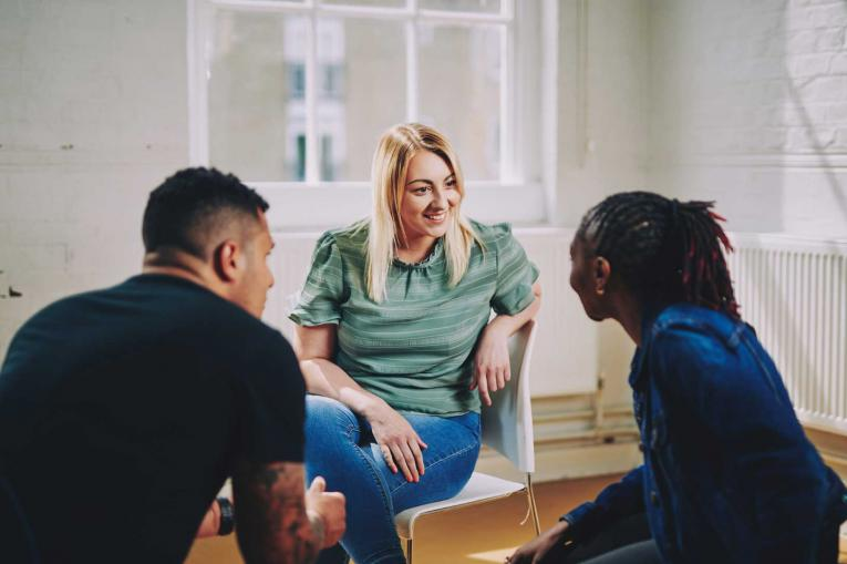 A woman and two men are sitting having a conversation