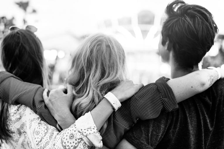 Three young people with their arms around each other