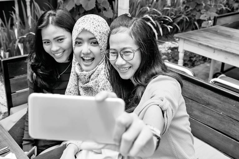 Three young people taking a group selfie