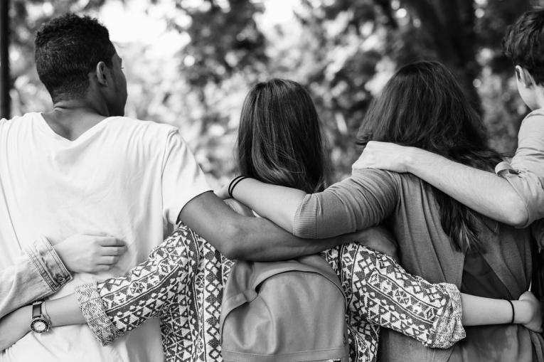 group of teenagers with their arms around one another