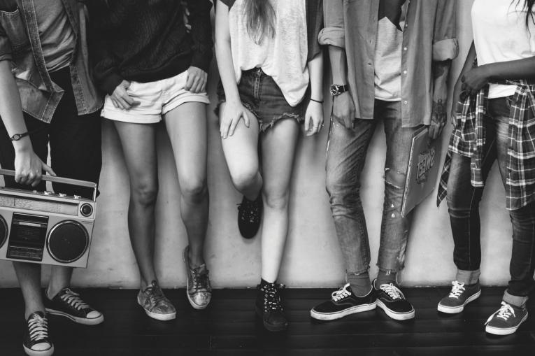 bottom halves of a group of teenagers standing around in trainers