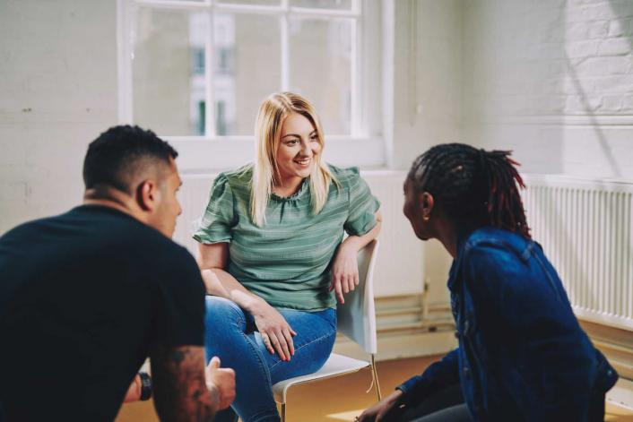 woman smiling sitting on a chair talking to two people