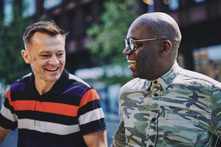 two men talking and smiling
